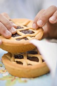 Child's hands holding chocolate tartlet