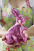 Woman holding Easter Bunny in pink foil