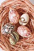 Decorated chocolate eggs in Easter nest (overhead view)