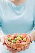 Woman holding Easter nest full of coloured sugar eggs