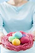 Woman holding Easter nest full of coloured Easter eggs