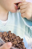 Child eating chocolate buttons out of plastic tub