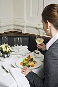Woman drinking white wine with salad in restaurant