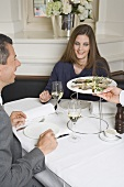Waiter serving fresh oysters to man & woman in restaurant