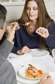 Man offering woman fried prawn in restaurant