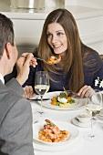 Man offering woman prawn on fork in restaurant