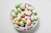 Pastel-coloured sugar eggs in white dish