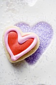 Biscuit on purple sugar in heart-shaped biscuit mould