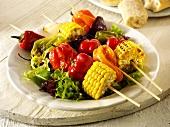 Colourful vegetable kebabs on salad leaves