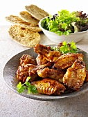 Grilled chicken wings with salad leaves and bread