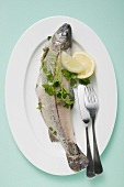 Trout with parsley, lemon wedges & fish knife & fork on plate