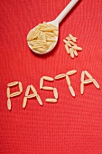 The word 'Pasta' written in pasta, pasta on wooden spoon