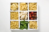 Various types of pasta, tomatoes and basil in type case