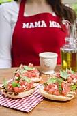 Bruschetta with tomato salsa, woman in background