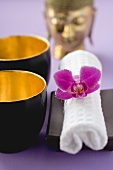 Two bowls, towel with orchid, statue of Buddha