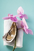 Fresh oyster with pearl on towel, orchids