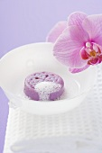 Soap with lather in white bowl on towel, orchid