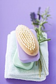 Brush and bars of soap on towel, sprig of lavender