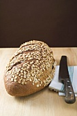 Wholemeal bread with rolled oats, tea towel, bread knife