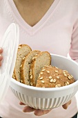 Woman holding oat bread in food storage container