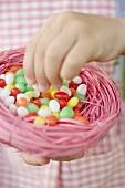 Child's hands holding Easter nest full of coloured sugar eggs