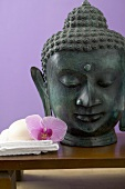 Orchid & soap on white towel beside statue of Buddha