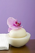 Orchid on soap in bowl beside white towel