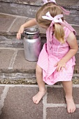 Small girl with milk can on stone steps