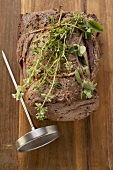 Roast beef with herbs, meat thermometer (overhead view)