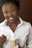 Woman holding glass of latte macchiato