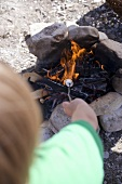 Child grilling marshmallows over camp-fire