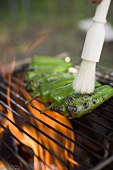 Green chillies on barbecue grill rack with brush