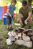 Father and son grilling fish over camp-fire