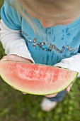 Small girl holding slice of watermelon with bites taken (overhead)