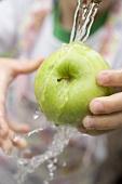 Kind hält grünen Apfel unter Wasserstrahl