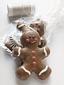 Two chocolate-coated gingerbread men, one in cellophane bag