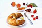 Croissant, jam and fresh fruit for breakfast