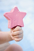 Child's hand holding a pink ice cream on a stick