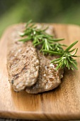 Fried pork sausagemeat with rosemary on chopping board