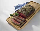 Roast beef with herb crust on chopping board