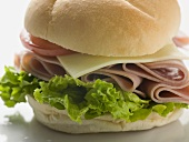 Bread roll filled with ham, cheese, lettuce & tomato (close-up)