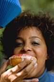 Woman biting into a doughnut (4th of July, USA)