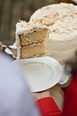 Man serving woman piece of coconut cake (4th of July, USA)
