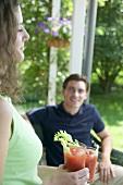 Junge Frau mit zwei Tomatendrinks, Mann im Hintergrund
