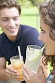 Young couple drinking iced tea and lemonade