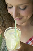 Young woman drinking lemonade through a straw