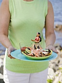 Woman holding plate of crab claws and dip on beach