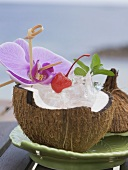 Ice cubes, cocktail cherry and orchid in coconut half