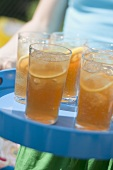 Person serving several glasses of iced tea on a tray