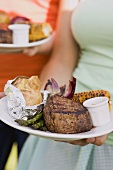 Two women holding plates of grilled steak & accompaniments